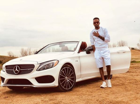 9ice posing with the white Benz